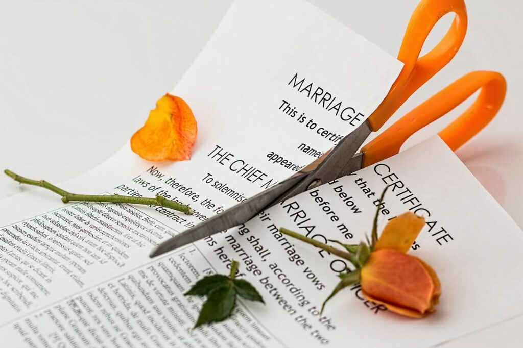 Image of orange scissors cutting through a marriage certificate and orange rose stem, indicating the tax issues with the alimony deduction.