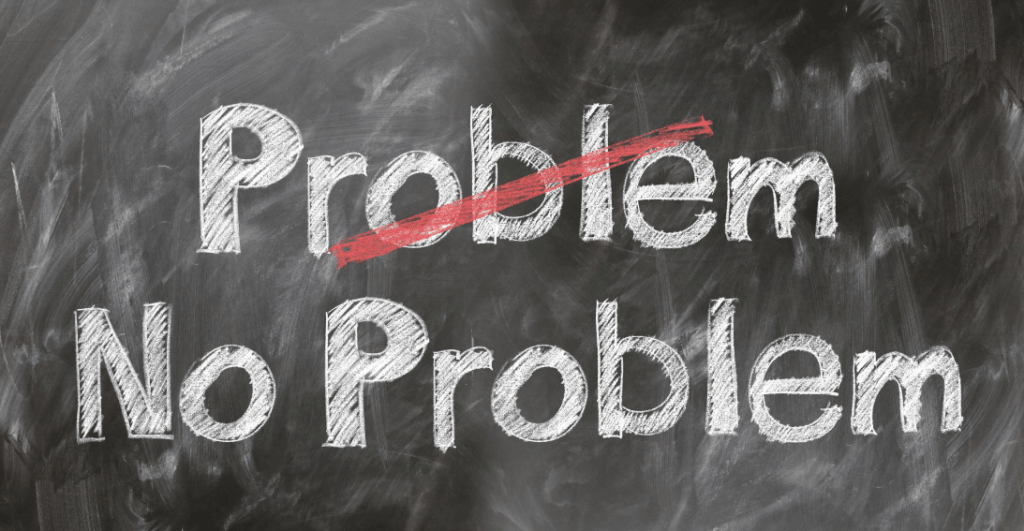 """Image of a blackboard with the words PROBLEM No Problem, and """"PROBLEM"""" has a red slash through it, indicating the hope that tax issues don't become a problem."""