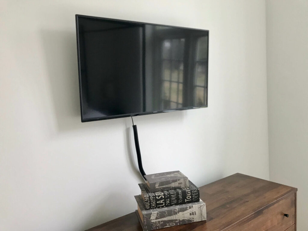 Image of a black television on a white wall with three books stacked on a dresser under it.
