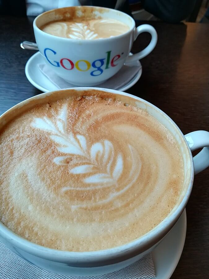 Photo of two mugs of coffee, with one of the mugs having a Google logo.