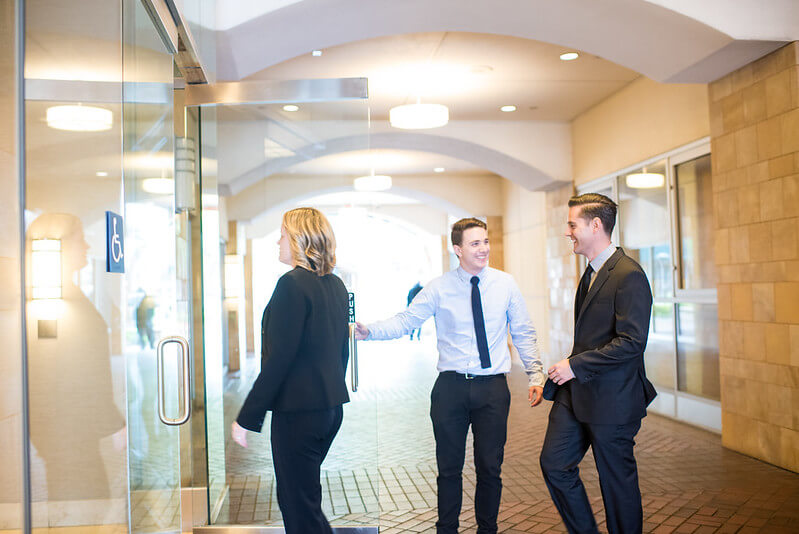 Image of happy employees entering through glass doors of an office building, part of their employee perks program.
