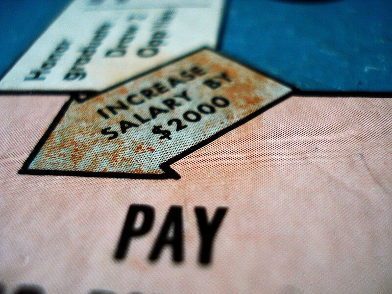 Photo of a game board with an arrow that says INCREASE YOUR SALARY BY $2000 inside, and the word PAY.