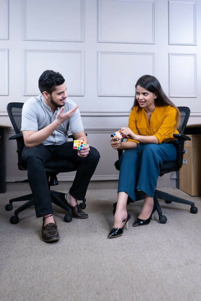 Image of two employees working on a rubix cube, discussing employee perks.