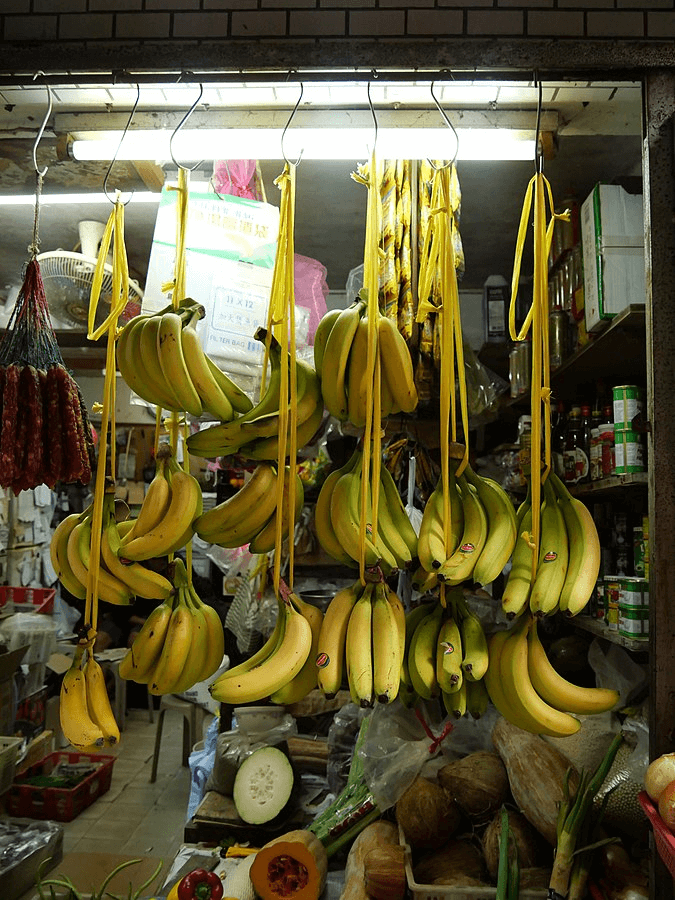Image of bananas hanging in a market, one strategy for marketing.
