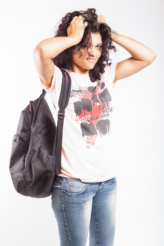 Image of a person carrying a backpack, pulling her own hair, as though she is experiencing secondhand stress.