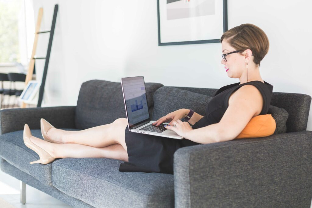 Image of worker sitting on couch, legs up, on computer, without any stress.