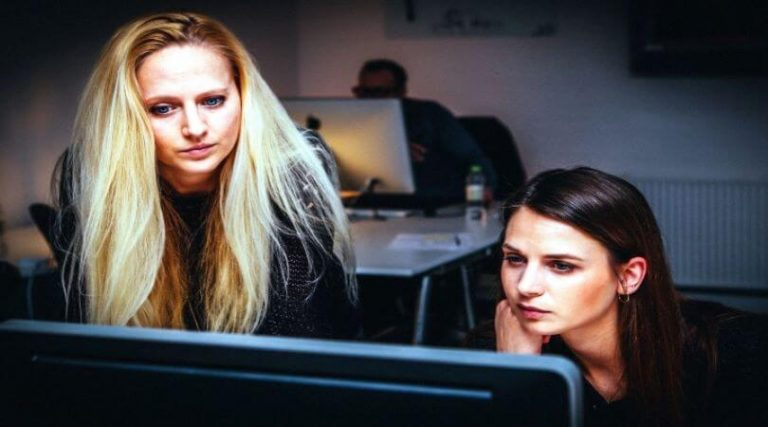 Photo of two women in the workplace looking at a computer together.