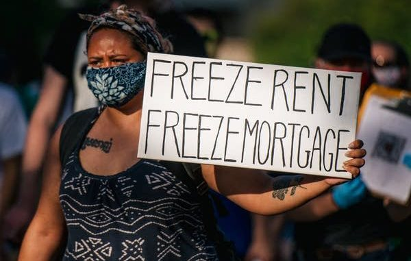 Photo of a woman holding a sign that says FREEZE RENT FREEZE MORTGAGE.