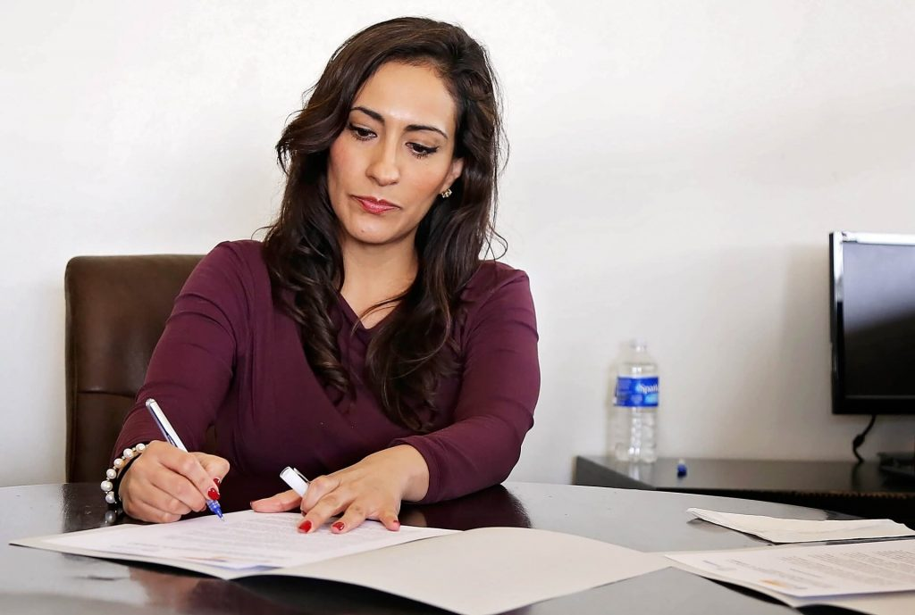 Photo of a female employee writing on a document.