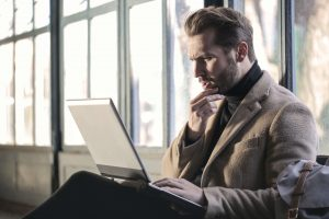 Photo of a man looking at his computer with a pensive expression.