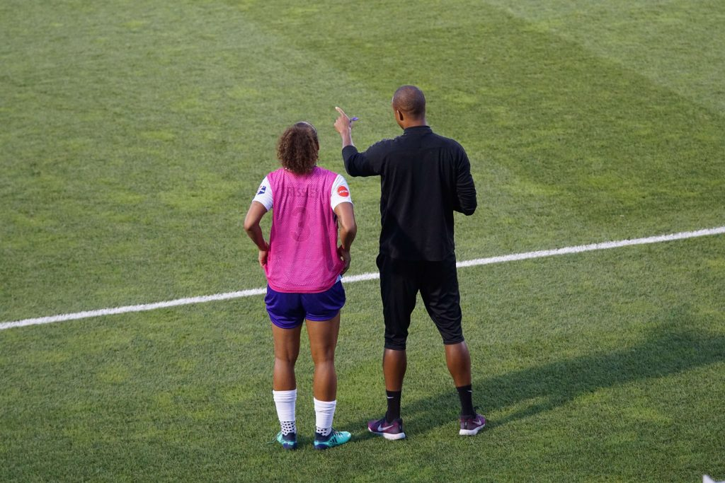 Image of a coach standing at the edge of a playing field giving his team member some advice.