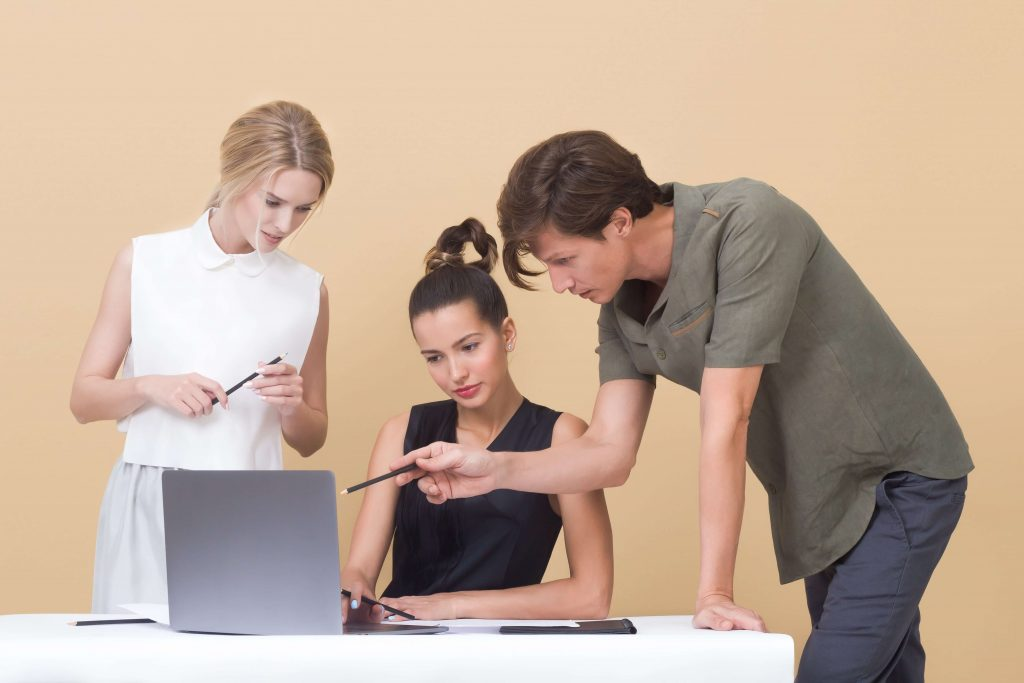 Photo of three people (two standing, one sitting) looking at a computer screen.