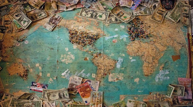 Image of a world map with different types of money (compensation) sprinkled around.