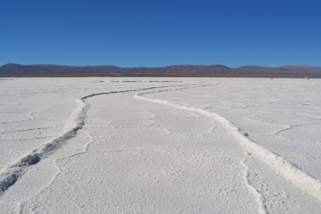 Photo of a salt road with mountains and a blue sky in the background.