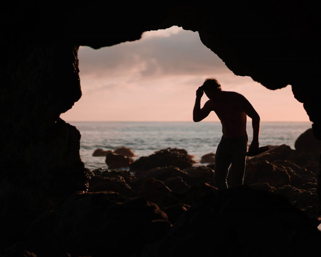 Photo of the silhouette of a person standing in a cave with a body of water in the background.