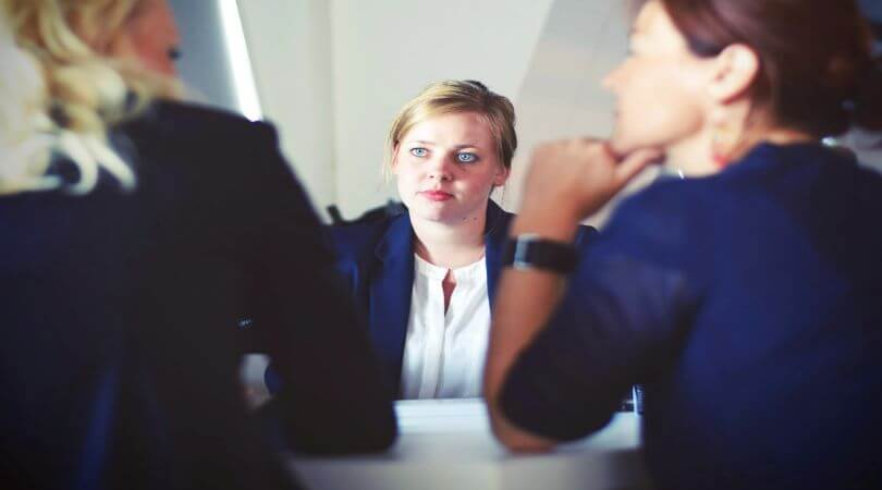 Photo of a woman in a white shirt and blazer sitting in front of two other women in dark colors and looking at the woman to her right.