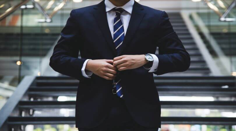 Photo of a sales professional buttoning up his suit in front of his striped tie.