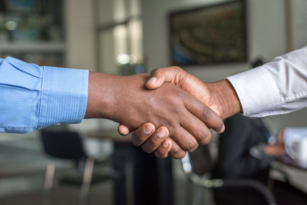 Photo of two arms wearing dress shirts extended in a handshake.