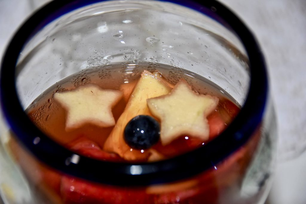 Photo of a glass of fruit water with red, white, and blue hues and star-shaped fruit.