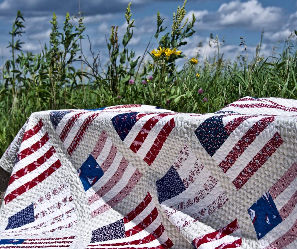 Photo of an American flag quilt in the middle of a grassy field.