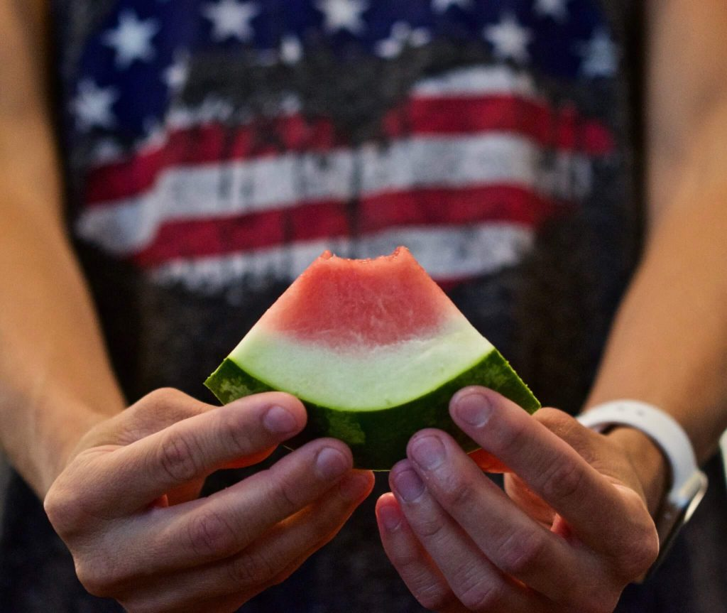 Photo of a person holding a slice of watermelon in front of a patriotic shirt.