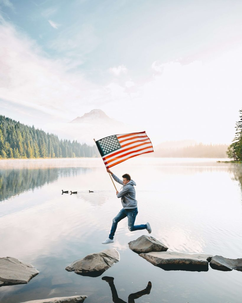 Photo of a man in a hoodie, jeans, and white shoes jumping across rocks in a body of water holding an American flag.