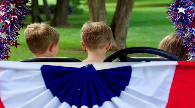 Photo of three children sitting in facing away from the camera with a red, white, and blue flag behind them.