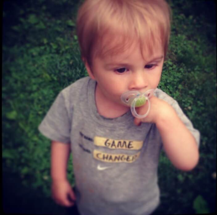 Photo of a small child with a pacifier in his mouth and the words GAME CHANGER on his t-shirt.