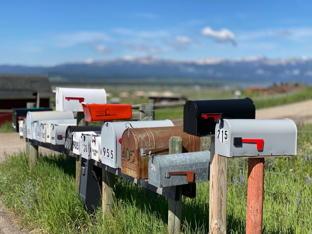 Photo of a row of mailboxes on a country road with blue skies in the background.