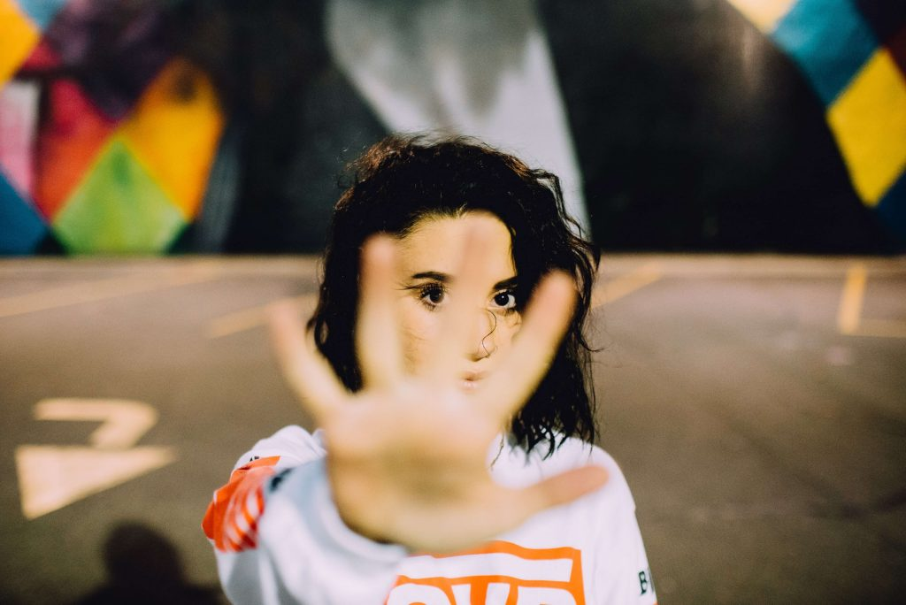 Photo of a woman holding her hand out in front of the camera in a gesture of opposition.
