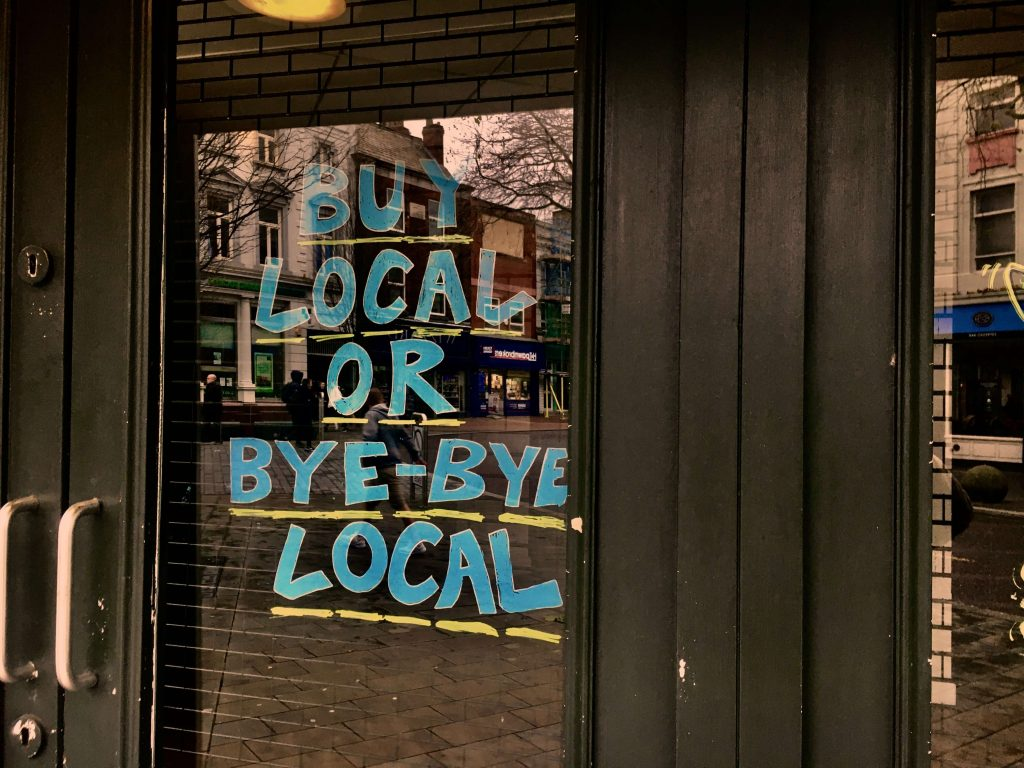 Photo of the front of a shop with BUY LOCAL OR BYE-BYE LOCAL written in blue chalk pain on the door.