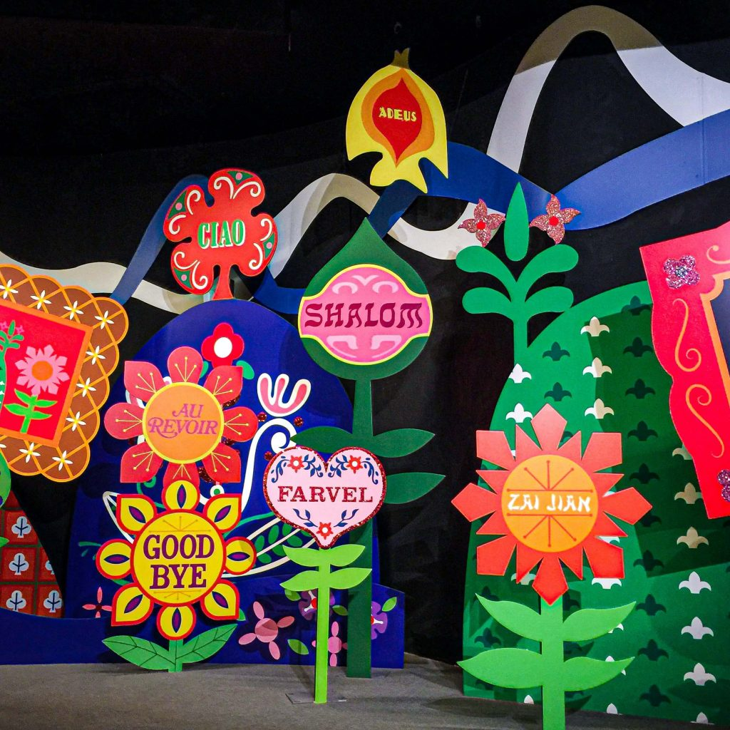 Photo of a bunch of colorful signs with abstract flowers and the words GOODBYE in various languages.