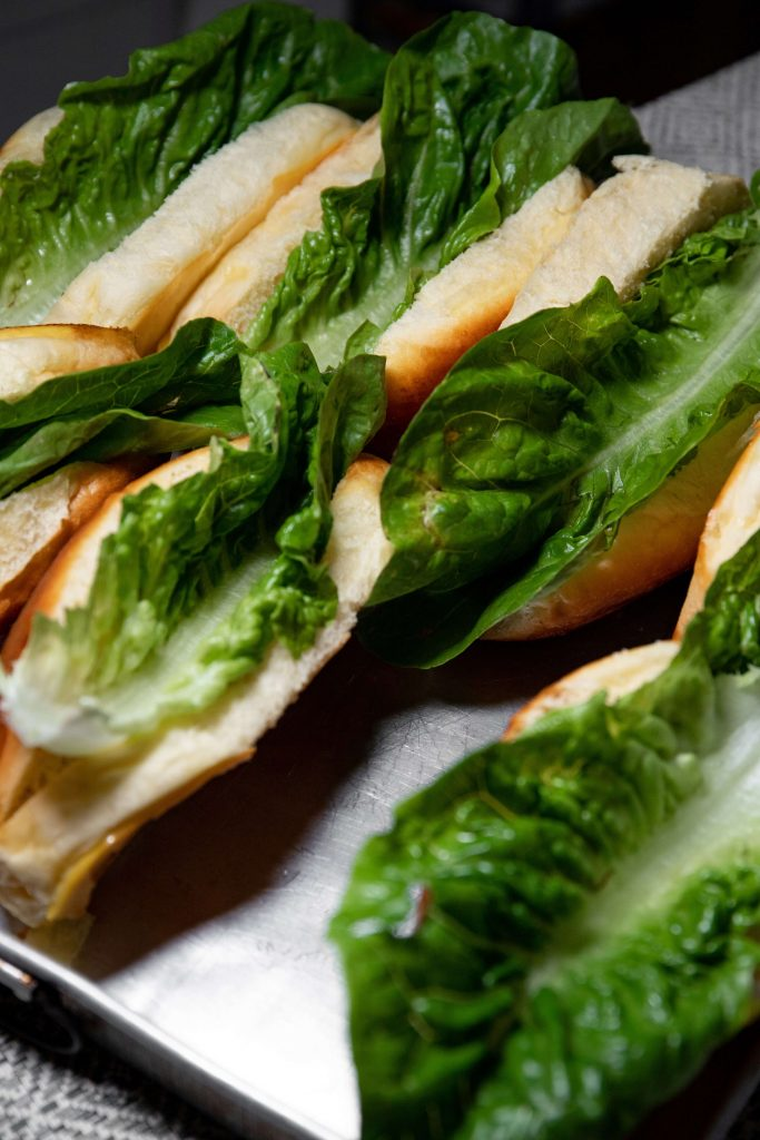 Photo of empty hotdog buns with lettuce in them.