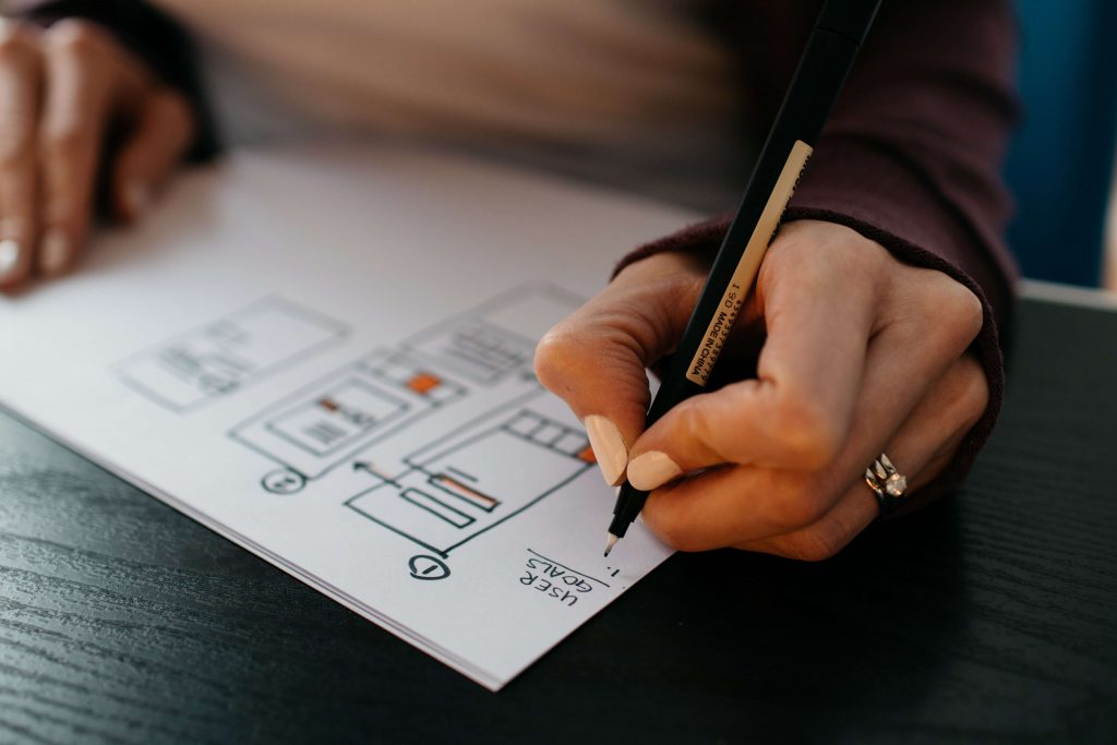 Photo of a person holding a pen and drawing sketch plans.