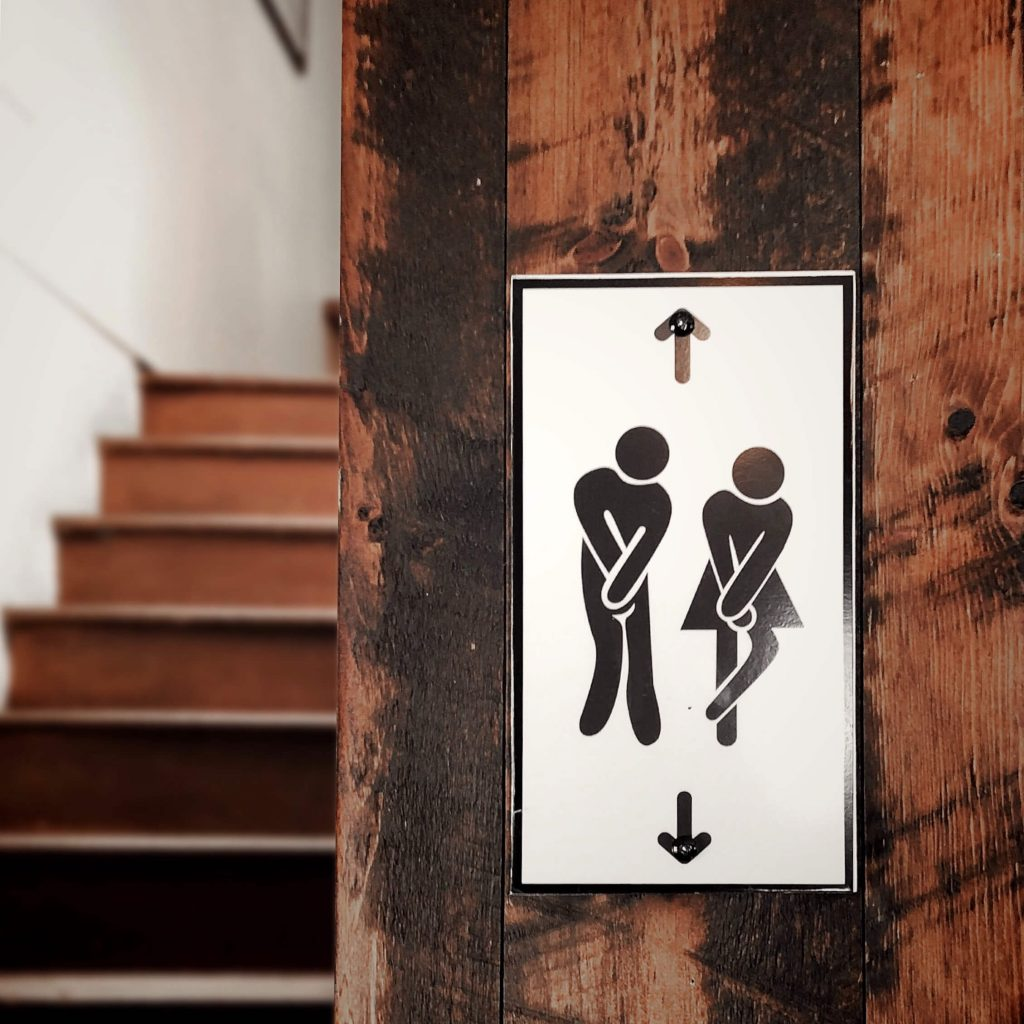 Photo of a staircase with a sign pointing above to a men's room and below to the women's room.
