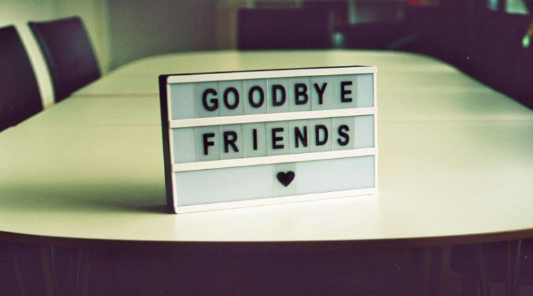 Photo of a conference room table with a plaque that says GOODEBYE FRIENDS with a small heart below the words.