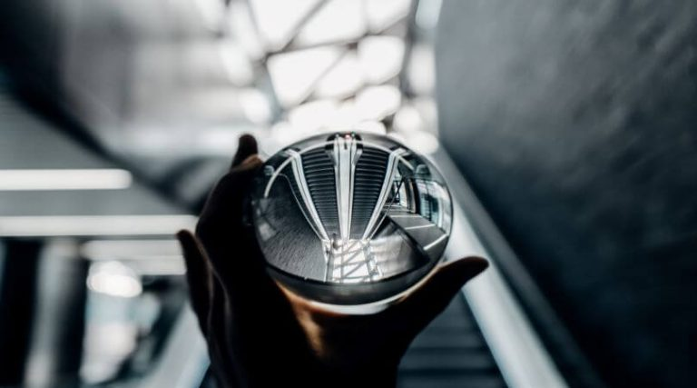 Image of hands holding a crystal ball in front of a staircase leading up.