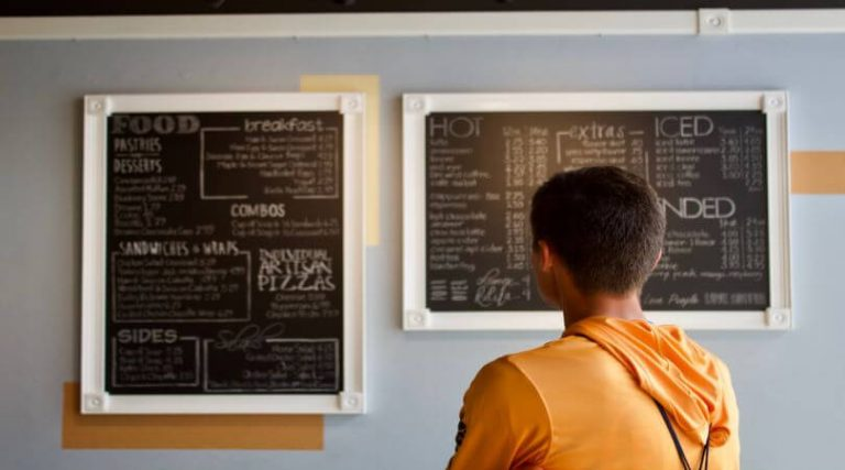Photo of a person from behind who is looking at menus on a wall.