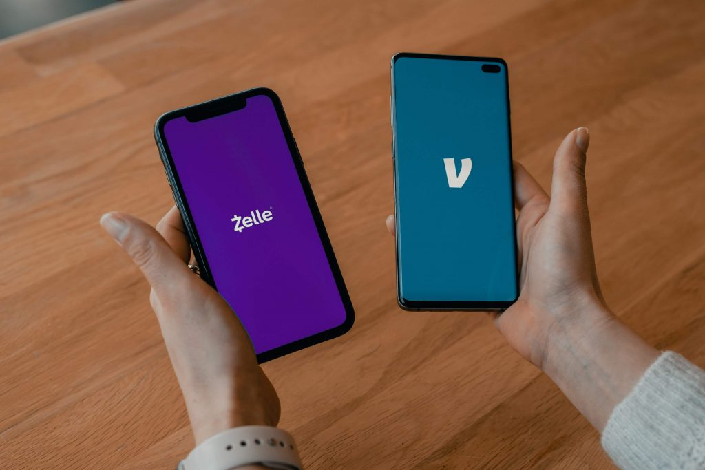Photo of two hands, the one on the left holding a smartphone with a Zelle app, and the one on the right holding a smartphone with a Venmo app on the screen.
