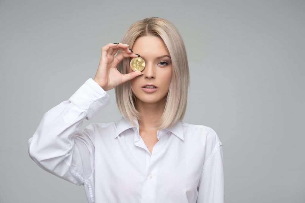 Photo of a blonde woman in a white shirt holding a Bitcoin piece in front of her right eye.
