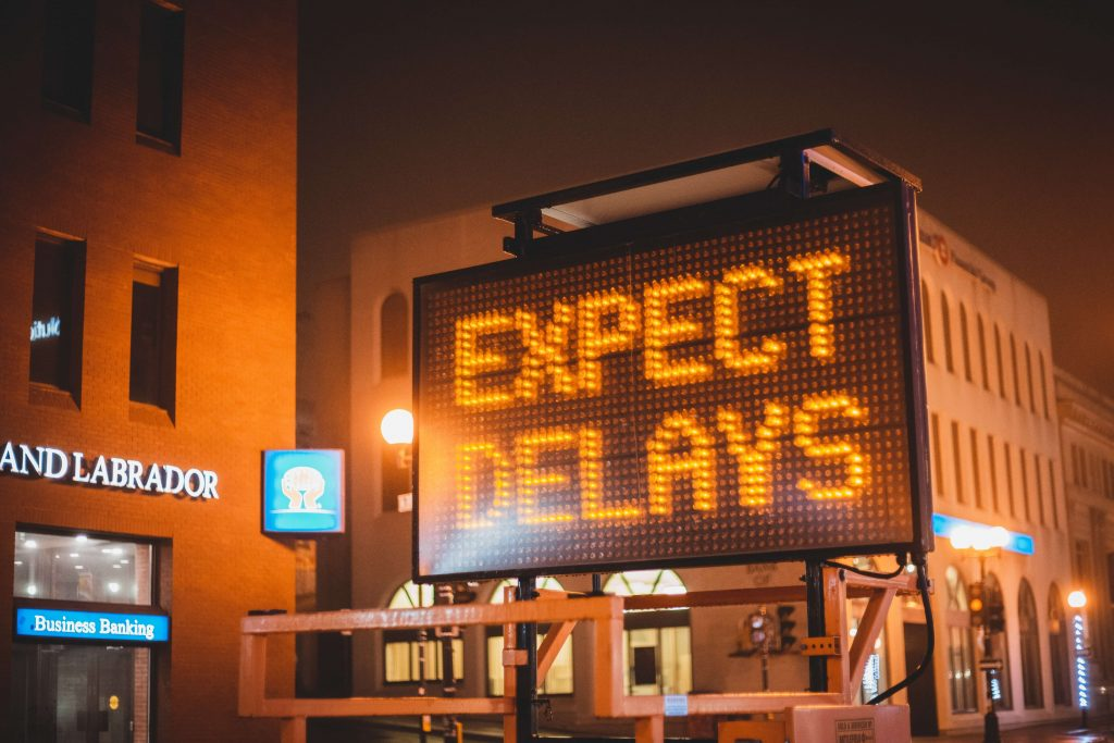 Photo of a traffic caution sign with the words EXPECT DELAYS.