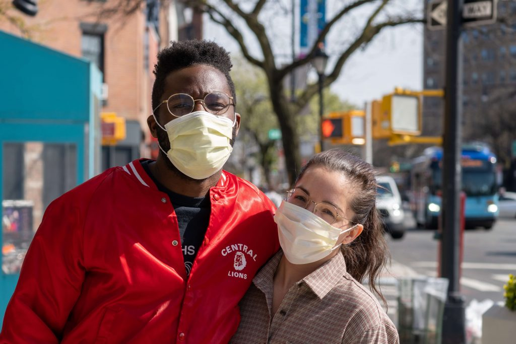 Photo of two people in a side-hug with masks on.