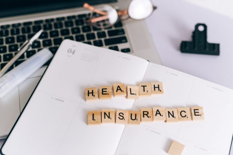 """Wooden blocks spelling out """"health insurance"""" on an open day planner"""